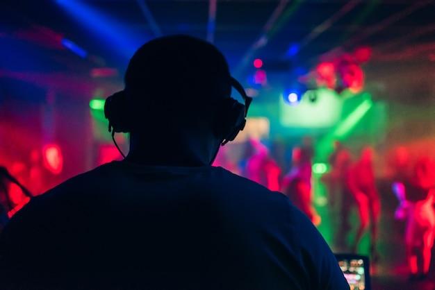 Dj występuje w klubie nocnym i gra muzykę