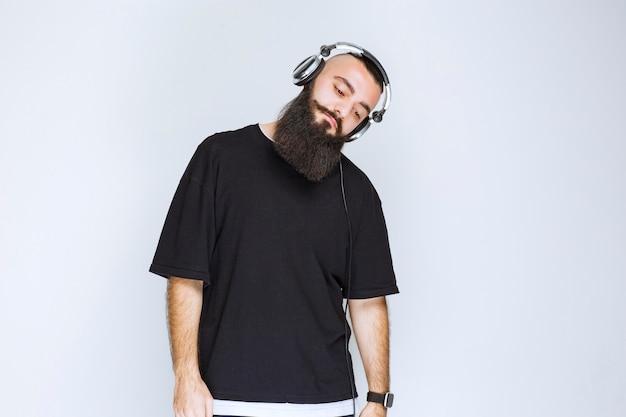 Dj z brodą ma na sobie słuchawki i śpi.