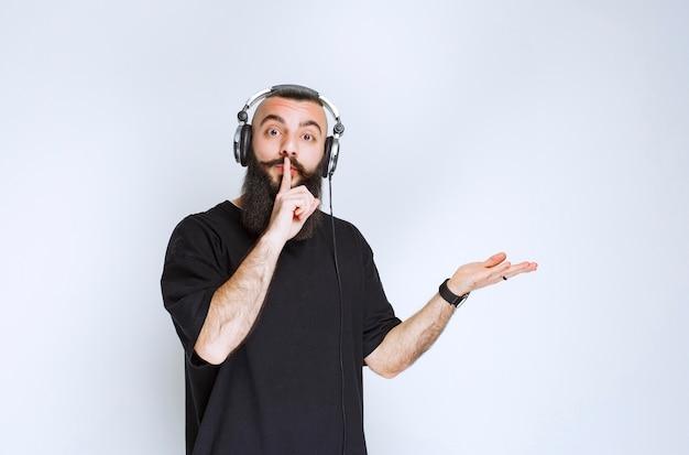 Dj z brodą, noszący słuchawki i wskazujący na prawą stronę.