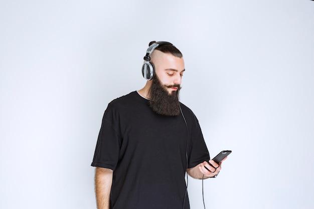 Dj z brodą w słuchawkach i ustawiający muzykę ze swojej playlisty na swoim smartfonie.