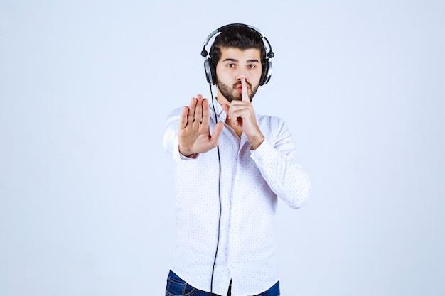 Dj ze słuchawkami proszący o ciszę