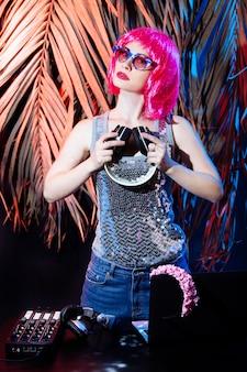 Dj ze słuchawkami, różowymi włosami i różowymi płytami winylowymi