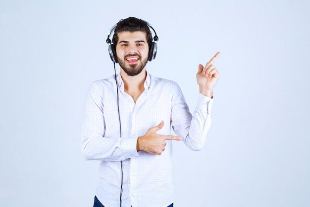 Dj ze słuchawkami tańczącymi i wskazujący na kogoś po prawej