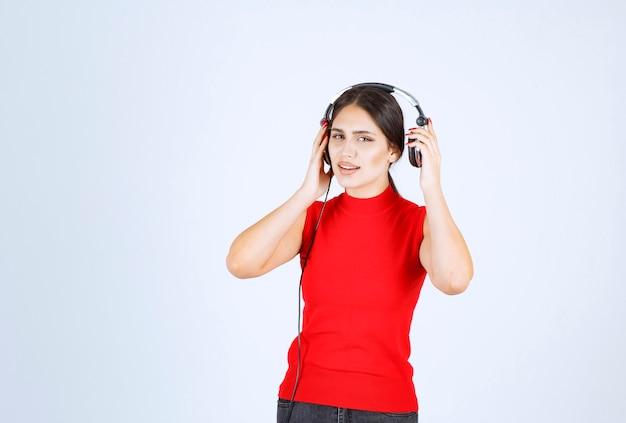 Dj ze słuchawkami wyciągając jedno ucho, aby dobrze słyszeć.