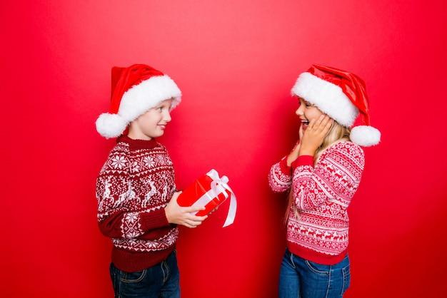 Dla ciebie! mały uroczy dżentelmen przygotował prezent dla uroczej małej damy, jest bardzo podekscytowana, zarówno w tradycyjnej dzianinowej odzieży, dżinsach, stojąc na czerwono