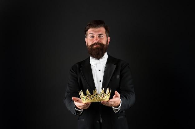 Dla was. nagroda za sukces w biznesie. główny menadżer. król stylu. brodaty mężczyzna nosi złotą koronę. elegancki mężczyzna w wizytowym stroju na specjalne wydarzenie. król partii. jest klientem vip. koncepcja użytkownika premium.