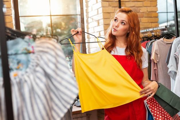 Dlaczego nie. wesoła piękna młoda dziewczyna, uśmiechając się i patrząc w dal podczas wizyty w sklepie z ubraniami i myśli o zakupie nowej bluzki