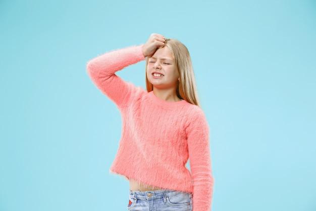 Dlaczego. piękny portret kobiety w połowie długości na modnym niebieskim tle. młoda emocjonalnie zaskoczona, sfrustrowana i oszołomiona nastolatka