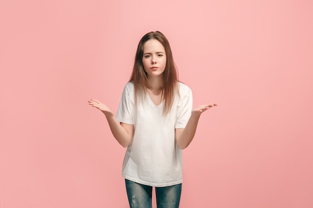 Dlaczego. piękny portret kobiety w połowie długości na modnym różu. młoda emocjonalnie zaskoczona, sfrustrowana i oszołomiona nastolatka
