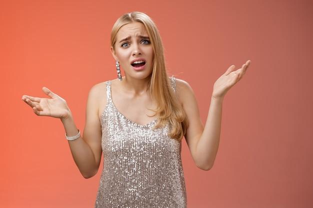Dlaczego wyjeżdżać wcześnie. zdenerwowana, narzekająca młoda atrakcyjna, zmartwiona blondyna narzekająca spojrzenie wypytywana rozczarowana podnoszenie rąk w bok konsternacja bez pojęcia marszczy brwi niezadowolone, czerwone tło.