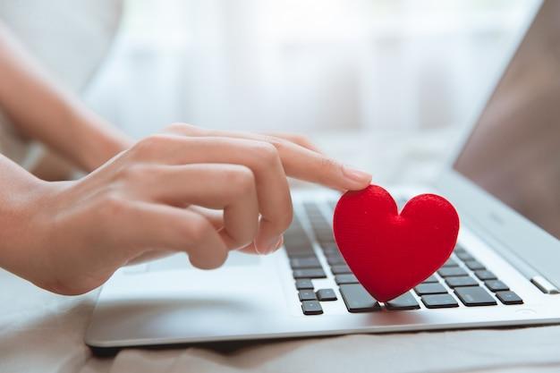 Dłoń dotykająca czerwonego serca na klawiaturze laptopa na czacie miłosnym flirt lub kochanka online w celu znalezienia pary randkowej podczas pobytu w domu sytuacja związana z pandemią koronawirusa