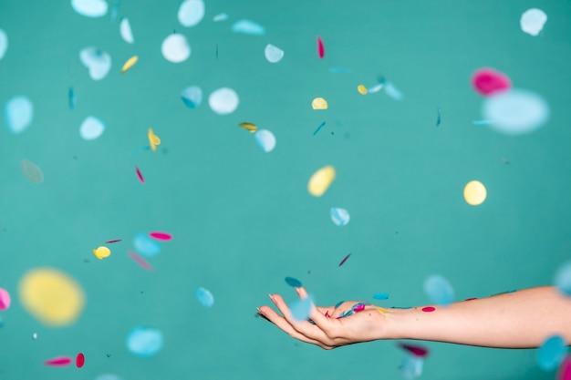 Dłoń dotykająca kolorowe konfetti