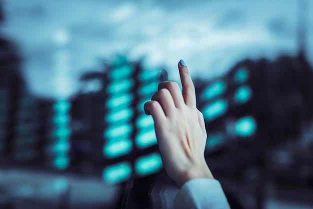 Dłoń dotykająca przezroczystego ekranu cyfrowego