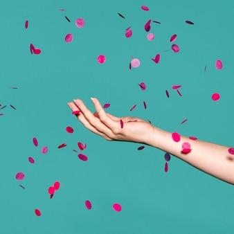 Dłoń dotykająca różowego konfetti