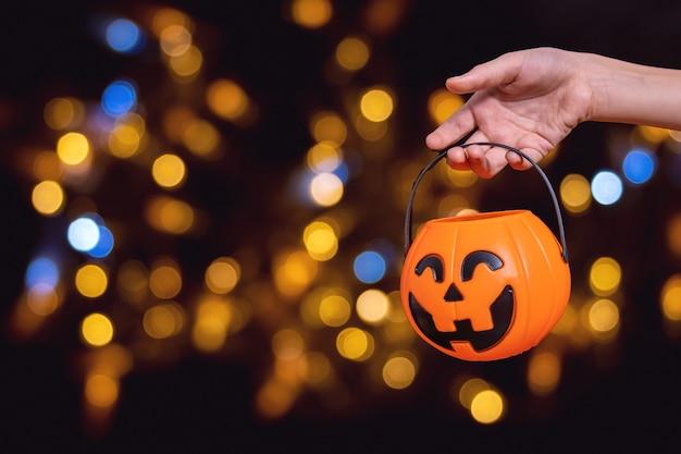 Dłoń dziecięca trzymająca pomarańczowy kosz w kształcie dyni, latarnia jacka na ciemnym tle z pięknym bokeh. czekam na cukierki na halloween. tradycję oszukać albo potraktować. koncepcja wesołego halloween