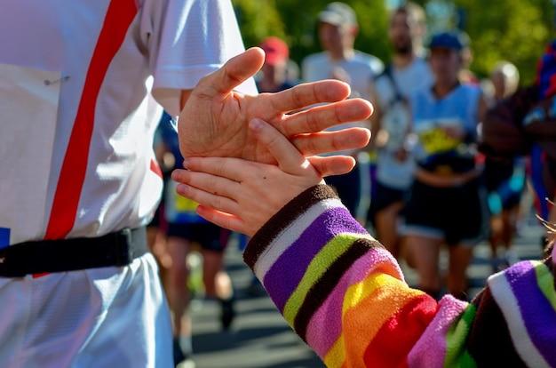 Dłoń dziecka dająca piątkę w wyścigu maratońskim