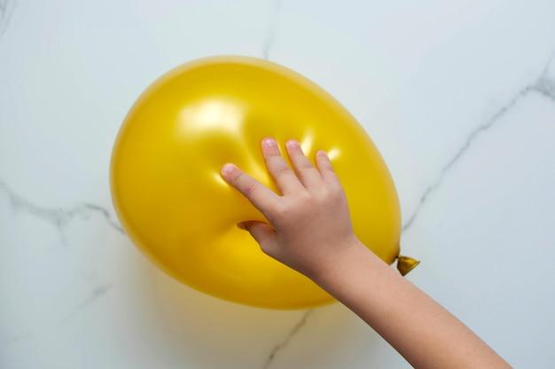 Dłoń dziecka gra w dotykową grę edukacyjną, próbując rozerwać balon.