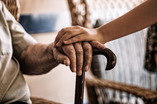 Dłoń dziecka nad dłonią starego człowieka trzymającą laskę.