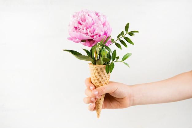 Dłoń dziecka trzyma rożek waflowy z różową piwonią. twórcze martwa natura z kwiatkiem wystającym ze stożka waflowego. poziome zdjęcie