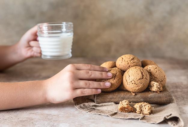 Dłoń dziecka wyciąga z deski ciasteczka owsiane zdrowa przekąska lub deser