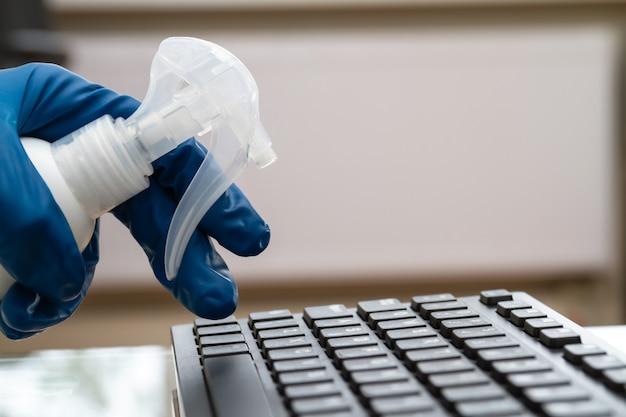 Dłoń dziewczynki w niebieskiej rękawicy ochronnej czyści klawiaturę środkiem dezynfekującym i ściereczką