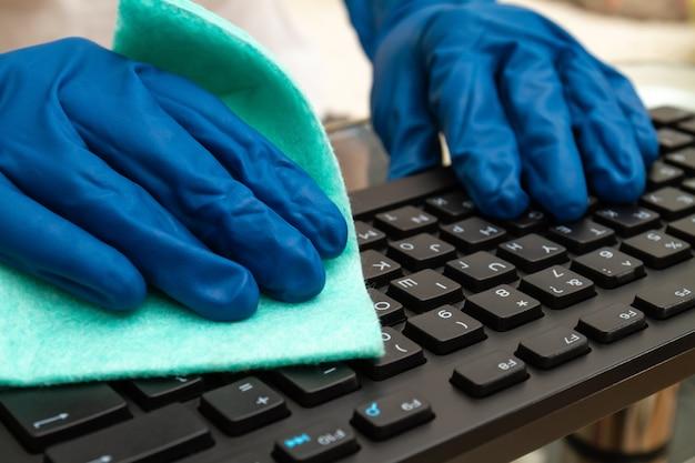 Dłoń dziewczynki w niebieskiej rękawicy ochronnej czyści klawiaturę szmatką