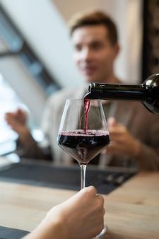Dłoń dziewczyny siedzącej przy serwowanym stole przed swoim chłopakiem podczas kolacji i trzymająca kieliszek, podczas gdy kelner nalewa do niego czerwone wino