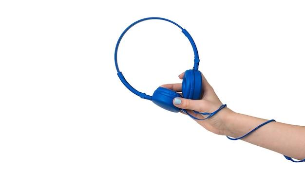 Dłoń dziewczyny w niebieskich słuchawkach i drutem owiniętym wokół jej ramienia. sprzęt do słuchania muzyki.