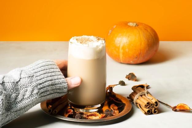 Dłoń dziewczyny w szarym swetrze bierze w szklance latte z przyprawami z dyni