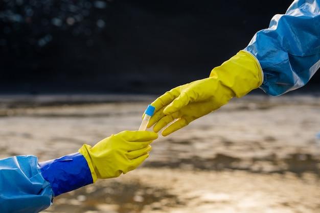 Dłoń ekologa w rękawiczce w ochronnym kombinezonie pobierająca butelkę z próbką toksycznej wody z butelki jej kolegi przeciwko zanieczyszczonej rzece