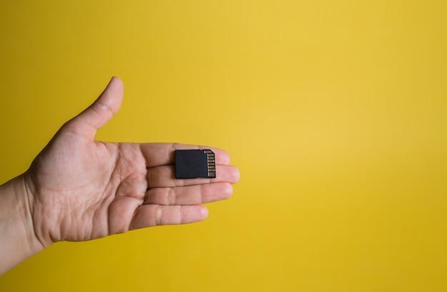 Dłoń i żeton na żółtym polu z wolnym miejscem. elektroniczna rejestracja ludności. odłupywanie ludzi. kontrola ruchu.