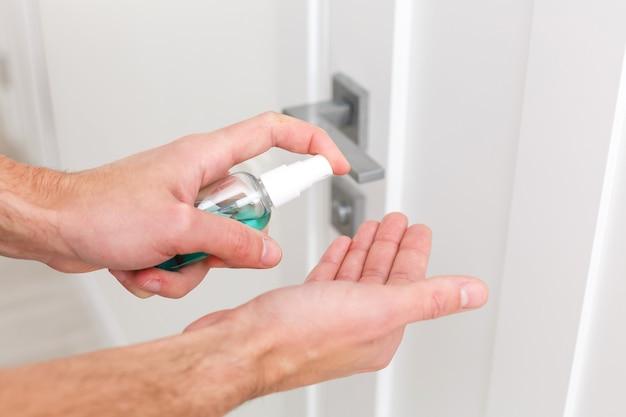 Dłoń jest traktowana środkiem antyseptycznym po klamce