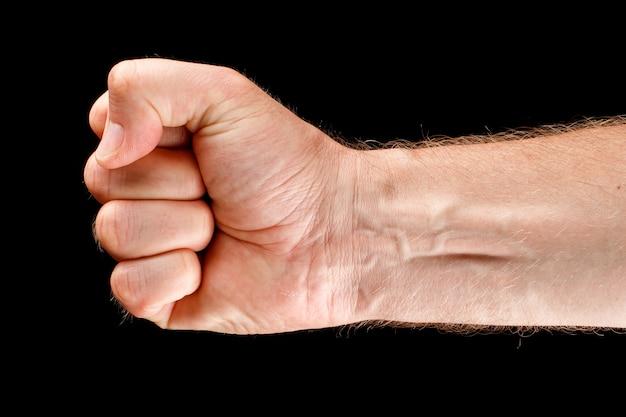 Dłoń jest zaciśnięta w pięść jako symbol siły i oporu