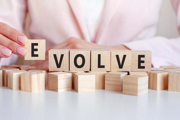 Dłoń kładzie drewnianą kostkę z literą evolve.