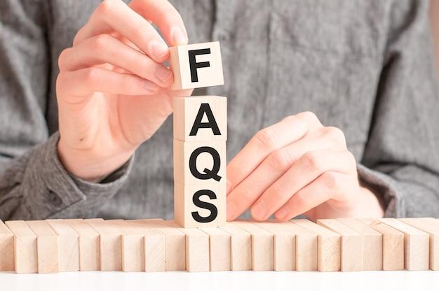 Dłoń kładzie drewnianą kostkę z literą f ze słowa faqs