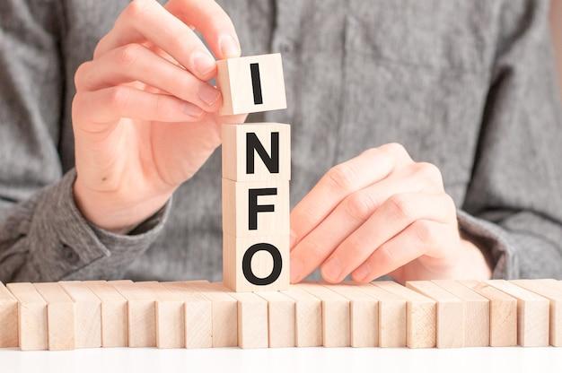 Dłoń kładzie drewnianą kostkę z literą i ze słowa info.