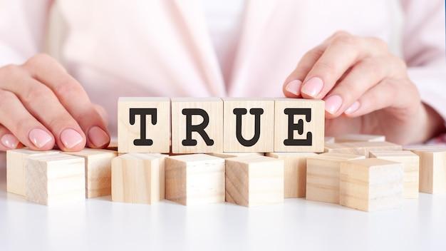Dłoń kładzie drewnianą kostkę z literą true. słowo napisane jest na drewnianych kostkach stojących na białej powierzchni stołu na różowym tle.