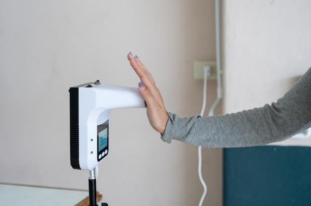 Dłoń kobiety bezdotykowy pomiar za pomocą automatycznego cyfrowego termometru na podczerwień