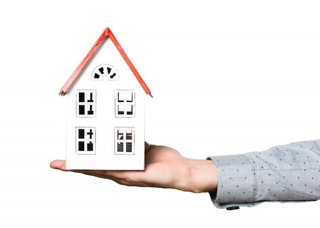 Dłoń mężczyzny trzyma mały dom