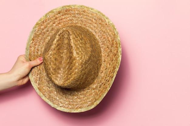 Dłoń młodej kobiety trzyma kapelusz słomy latem na różowym tle. tło mody. koncepcja letnia.
