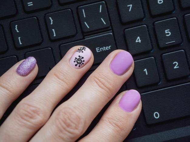 Dłoń na klawiaturze. kreatywny manicure z malowanym koronawirusem na paznokciach, z bliska