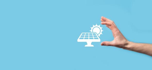 Dłoń na niebieskim tle trzyma symbol ikony paneli słonecznych. energia odnawialna, koncepcja stacji paneli słonecznych, zielona energia elektryczna.
