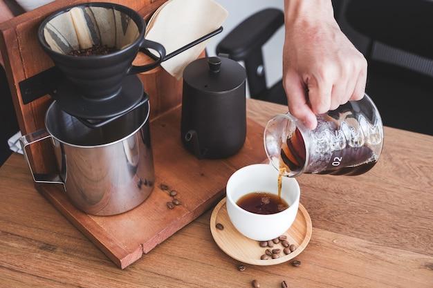 Dłoń nalewająca kroplówkę kawy do kubka