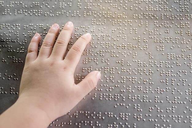 Dłoń niewidomego dziecka i palce dotykające liter brajlowskich na metalowej płytce