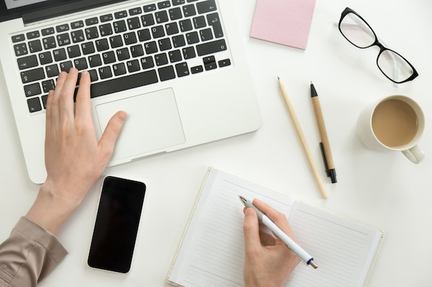Dłoń pracująca na laptopie, druga trzyma długopis
