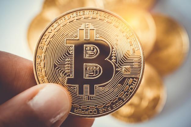Dłoń trzymaj symbol bitcoinów jako kryptowaluty pieniędzy cyfrowych.