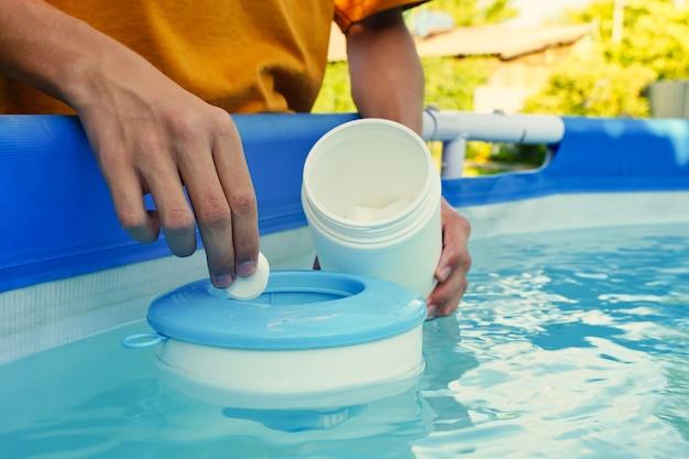 Dłoń trzymająca białe tabletki chloru nad odpieniaczem basenowym chlorowanie wody w basenie do...