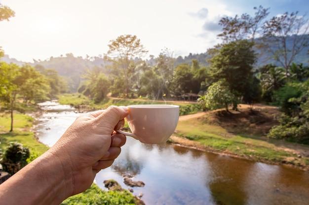 Dłoń trzymająca biały kubek kubków gorącej kawy espresso i widok przyrody górskiego krajobrazu rano z promieniami słonecznymi