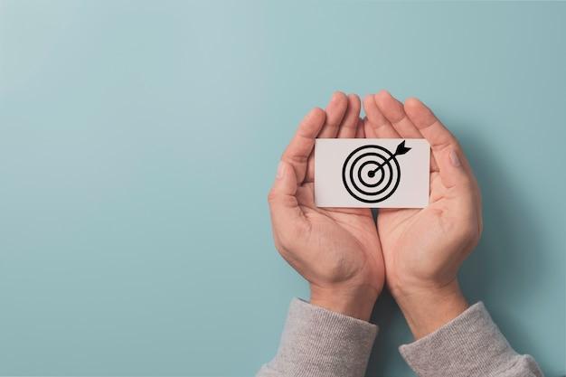 Dłoń trzymająca biały papier, który drukuje tarczę do rzutek ekranu ze strzałką na niebieskim tle i kopiuje przestrzeń, konfiguruje cele biznesowe i koncepcję docelową.