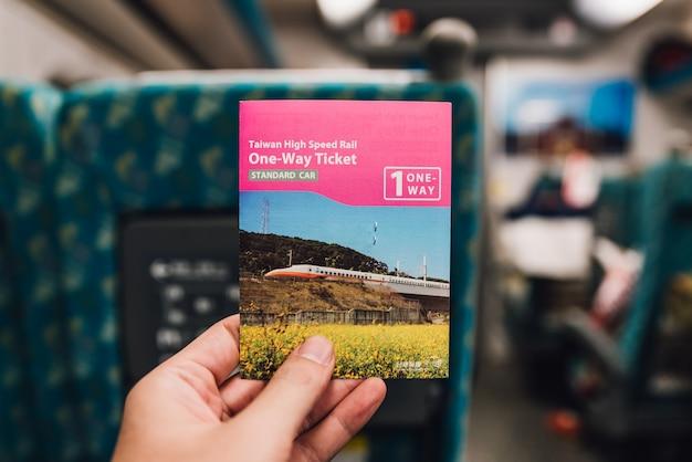 Dłoń trzymająca bilet tajwanu high speed train na platformie na tajwanie, tajpej.
